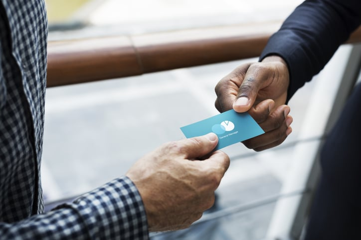 person-handing-over-business-card